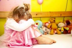 Nettes kleines Mädchen, das auf dem Bett sehr unglücklich sitzt lizenzfreies stockfoto