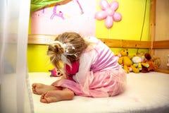 Nettes kleines Mädchen, das auf dem Bett sehr unglücklich sitzt lizenzfreie stockfotografie