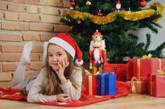 Nettes kleines Mädchen, das auf dem Plaid mit Geschenken durch Weihnachten t liegt Lizenzfreies Stockbild