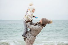 Nettes kleines Mädchen, das auf dem sandigen Strand spielt Glückliches Kindertragen lizenzfreie stockfotografie