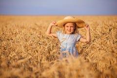 Nettes kleines Mädchen, das auf dem Sommergebiet des Weizens spielt Lizenzfreie Stockfotos