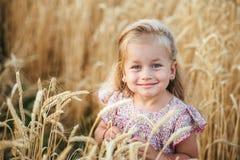 Nettes kleines Mädchen, das auf dem Sommergebiet des Weizens spielt Stockbilder