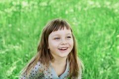 Nettes kleines Mädchen, das auf der grünen Wiese im Freien, glückliches Kindheitskonzept lacht stockbild