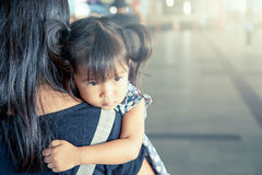 Nettes kleines Mädchen, das auf der Schulter ihrer Mutter stillsteht Lizenzfreie Stockfotos