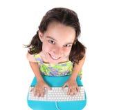 Nettes kleines Mädchen, das auf einer Computer-Tastatur schreibt lizenzfreie stockfotos