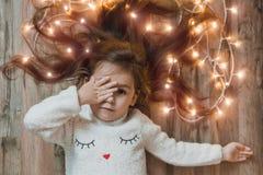 Nettes kleines Mädchen, das auf Flor mit heller Weihnachtsgirlande in ihrem Haar legt Weihnachtsporträt, gemütliche Art stockbilder