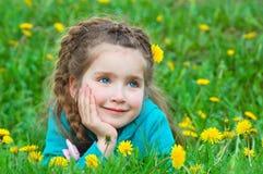 Nettes kleines Mädchen, das auf grünem Gras träumt Stockfotos