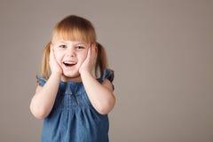 Nettes kleines Mädchen, das auf grauem Hintergrund lacht Lizenzfreies Stockfoto