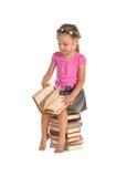 Nettes kleines Mädchen, das auf Stapel Büchern sitzt stockfoto