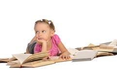 Nettes kleines Mädchen, das auf Stapel der Bücher liegt lizenzfreie stockfotos