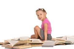Nettes kleines Mädchen, das auf Stapel der Bücher sitzt stockbild