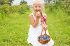 Nettes kleines Mädchen, das Blaubeeren isst Stockfotos