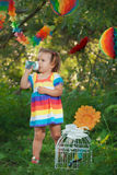 Nettes kleines Mädchen, das buntes Kleidertrinkwasser trägt stockbild