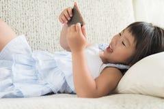 Nettes kleines Mädchen, das den Spaß, zum des Spiels am intelligenten Telefon zu spielen hat stockbild