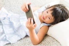 Nettes kleines Mädchen, das den Spaß, zum des Spiels am intelligenten Telefon zu spielen hat stockfoto