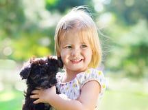 Nettes kleines Mädchen, das draußen Hundewelpen umarmt Stockfotografie