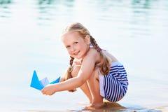 Nettes kleines Mädchen, das draußen Origamiboot hält Stockfoto