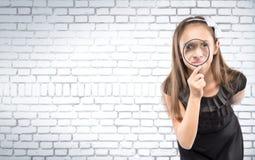 Nettes kleines Mädchen, das durch einen weißen Backsteinmauerhintergrund der Lupe schaut Pädagogisches Konzept Lizenzfreie Stockfotos