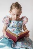 Nettes kleines Mädchen, das ein altes Rot liest Stockfoto