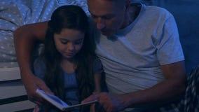 Nettes kleines Mädchen, das ein Buch mit ihrem Vater liest stock footage