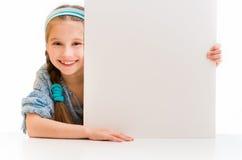 Nettes kleines Mädchen, das ein weißes Brett hält Lizenzfreies Stockbild