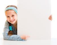 Nettes kleines Mädchen, das ein weißes Brett hält Lizenzfreies Stockfoto