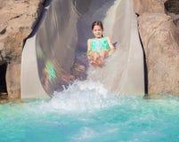 Nettes kleines Mädchen, das eine nasse Fahrt hinunter Wasserrutsche genießt Lizenzfreie Stockfotografie