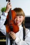 Nettes kleines Mädchen, das eine Violine Innen hält Stockfotos