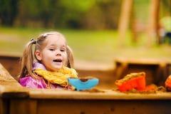 Nettes kleines Mädchen, das in einem Sandkasten spielt Stockbilder
