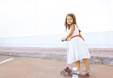 Nettes kleines Mädchen, das einen Roller reitet Stockbilder
