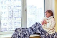 Nettes kleines Mädchen, das einen Teddybären umarmt Ein nettes Baby im Raum sitzt am Fenster im Winter Stockfotografie