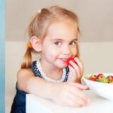 Nettes kleines Mädchen, das Erdbeere isst Lizenzfreies Stockfoto