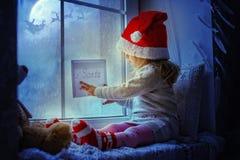 Nettes kleines Mädchen, das am Fenster mit einem Buchstaben zu Santa Claus sitzt lizenzfreies stockfoto