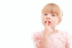 Nettes kleines Mädchen, das Finger vor Mund hält Lizenzfreie Stockbilder