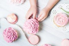 Nettes kleines Mädchen, das Geburtstagskleine kuchen in der Küche hält Festliches und Feiertagskonzept Lizenzfreie Stockfotos