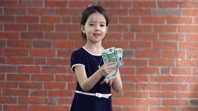 Nettes kleines Mädchen, das Geld zählt stock video