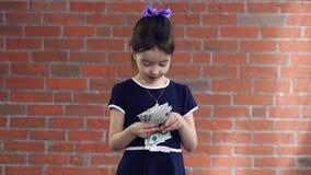 Nettes kleines Mädchen, das Geld zählt stock footage