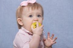 Nettes kleines Mädchen, das großen grünen Apfel isst Retro- Schuß Stockbilder
