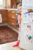 Nettes kleines Mädchen, das hinter Kühlschranktür in der Küche lächelt Stockfoto
