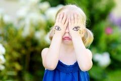 Nettes kleines Mädchen, das ihr Gesicht mit ihren Händen am Sommertag bedeckt Stockfotos