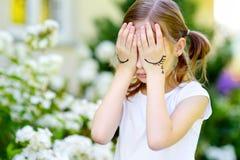 Nettes kleines Mädchen, das ihr Gesicht mit ihren Händen am Sommertag bedeckt Stockfoto