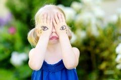 Nettes kleines Mädchen, das ihr Gesicht mit ihren Händen am Sommertag bedeckt Lizenzfreie Stockbilder