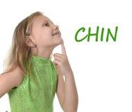 Nettes kleines Mädchen, das ihr Kinn in den Körperteilen in der Schule lernen englische Wörter zeigt Stockfotografie