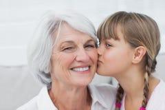 Nettes kleines Mädchen, das ihre Großmutter küsst Stockfotos