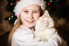 Nettes kleines Mädchen, das ihre Katze im Weihnachten umarmt Stockbild