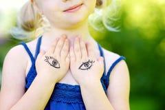 Nettes kleines Mädchen, das ihren Kasten mit ihren Händen am Sommertag bedeckt Stockfotos
