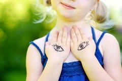 Nettes kleines Mädchen, das ihren Kasten mit ihren Händen am Sommertag bedeckt Stockfotografie