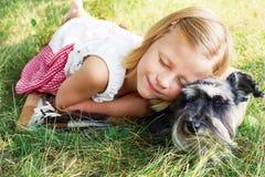 Nettes kleines Mädchen, das ihren kleinen Hund umarmt Lizenzfreie Stockfotografie