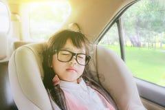 Nettes kleines Mädchen, das im Autositz schläft stockfotografie