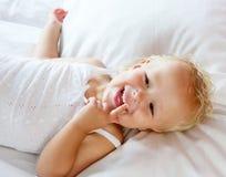 Nettes kleines Mädchen, das im Bett lacht Stockfoto